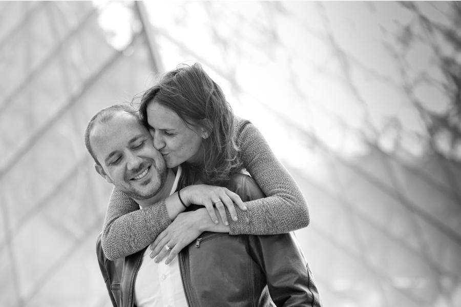 Couple qui s'enlace devant la pyramide du Louvre lors d'une session photo à Paris.